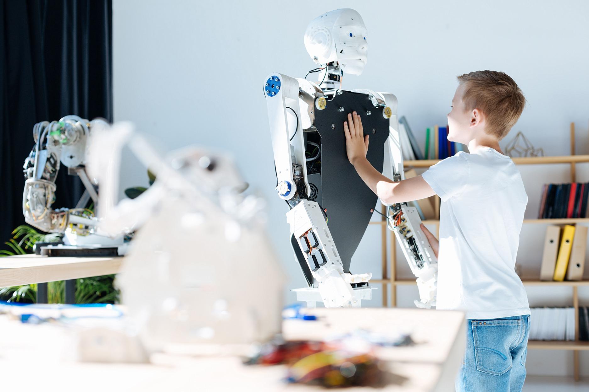 Boy touching a white robot